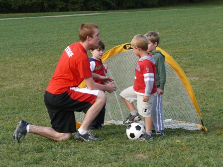 Photo of a coach with little soccer players